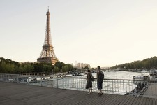 Couple watching the eiffel tower from across The Seine
